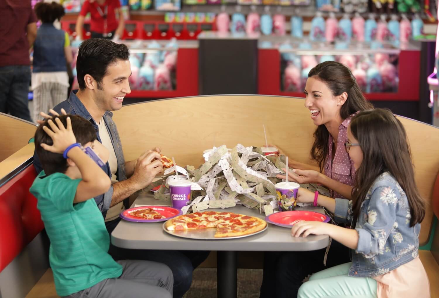 Family eating pizza with table full of tickets